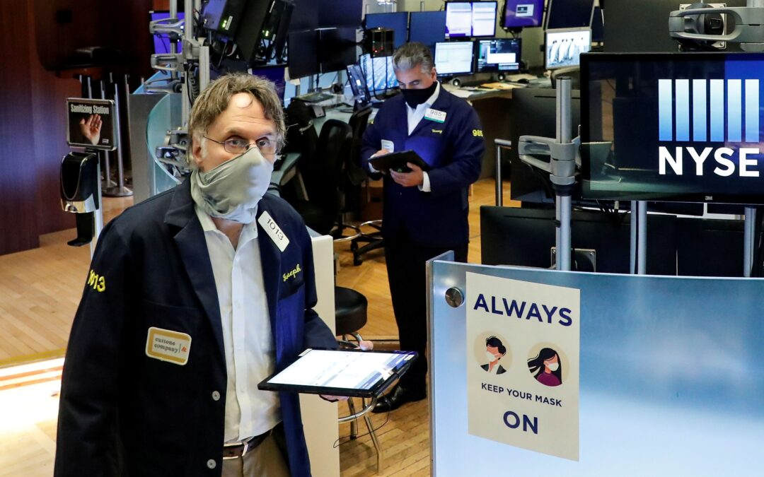 Traders wearing masks work, on the first day of in person trading since the closure during the outbreak of the coronavirus disease (COVID-19) on the floor at the New York Stock Exchange (NYSE) in New York, U.S., May 26, 2020. REUTERS/Brendan McDermid TPX IMAGES OF THE DAY